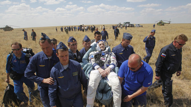 Russian space agency rescue team carry U.S. astronaut Donald Pettit, center,  shortly after the landing of the Russian Soyuz TMA-03M space capsule at the south-east of the Kazakh town of Dzhezkazgan, Kazakhstan, Sunday, July 1, 2012. The Soyuz capsule, which carried two astronauts and Russian cosmonaut safely returned to Earth on Sunday after a half-year stint on the international space station, with a landing on the Kazakh steppe. (AP Photo/Mikhail Metzel, pool)