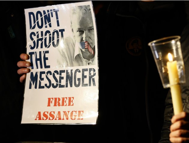 A supporter holds a banner as he waits for Julian Assange, founder of WikiLeaks to speak to the media and members of the public from a balcony at the Ecuadorian Embassy in London, Thursday, Dec. 20, 2