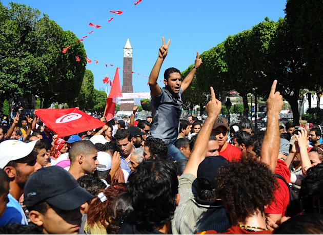 Protesters gather on the main avenue of Tunis after the leader of a leftist Tunisian opposition party, Mohammed Brahmi, was gunned down as he left home, in Tunisia, Thursday, July 25, 2013. Brahmi, 58