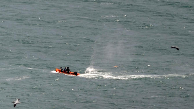 """Police in inflatable rubber boats shoot at a shark off Muriwai Beach near Auckland, New Zealand, Wednesday, Feb. 27, 2013, as they attempt to retrieve a body following a fatal shark attack. Police said a man was found dead in the water after being """"bitten by a large shark."""" (AP Photo/Ross Land) NEW ZEALAND OUT, NO SALES"""