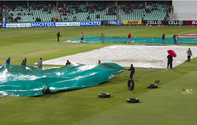 Ground staff put on the covers as rain comes down delaying play in the cricket T20 International cricket match between Australia and South Africa in Durban