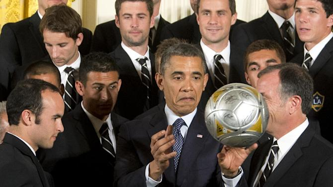 President Barack Obama, center, flanked by LA Galaxy forward Landon Donovan, left, and coach Bruce Arena, right, throws the soccer ball to the crowd during a ceremony in the East Room of the White House in Washington, Tuesday, March 26, 2013, honoring the Stanley Cup hockey champion Los Angeles Kings and the Major League Soccer champion LA Galaxy for their 2012 championship seasons.   (AP Photo/Manuel Balce Ceneta)