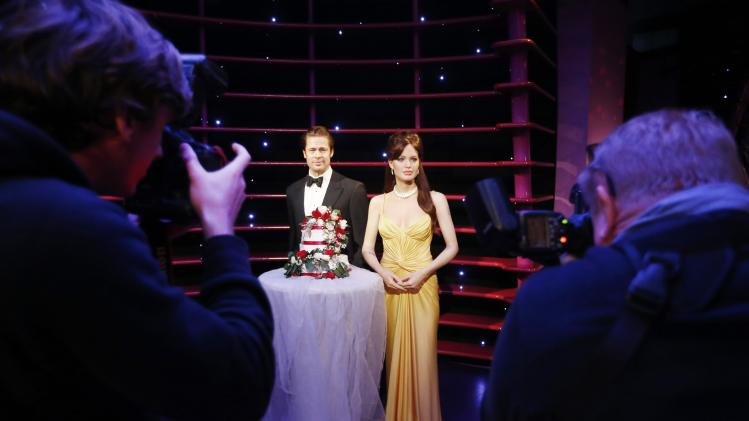 Wax models of actors Brad Pitt and Angelina Jolie are photographed with a wedding cake in celebration of their recent wedding, at the Madame Tussauds attraction in Sydney