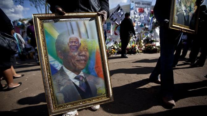 Street-traders sell pictures of Nelson Mandela that alternate images depending on the angle they are viewed at, in front of the wall of get-well messages and flowers left outside the Mediclinic Heart Hospital where former South African President Nelson Mandela is being treated in Pretoria, South Africa Thursday, July 11, 2013. Nelson Mandela is responding to treatment and the 94-year-old's condition remains critical but stable after more than a month in the hospital, South Africa's president said Wednesday. (AP Photo/Ben Curtis)