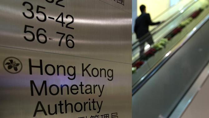 A security guard walks past a directory board of Hong Kong Monetary Authority (HKMA) in Hong Kong