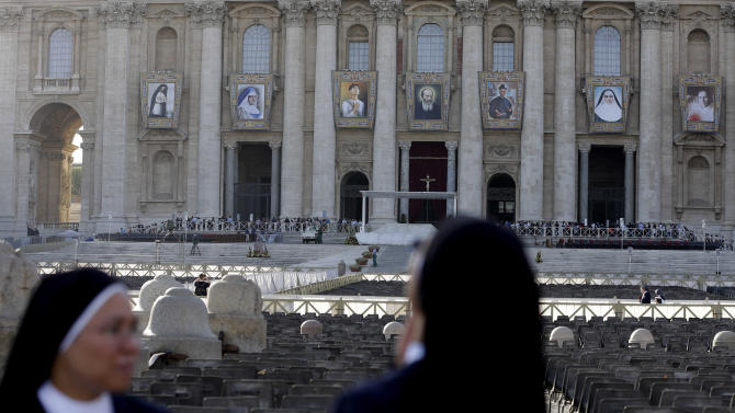 Two nuns look at tapestries of saints-to-be from left; Kateri Tekakwitha, Maria del Carmen, Pedro Calungsod, Jacques Berthieu, Giovanni Battista Piamarta, Mother Marianne Cope, and Anna Shaeffer hanging from St. Peter's Basilica at the Vatican, Saturday, Oct. 20, 2012. The seven will be declared saints in a ceremony presided over by Pope Benedict XVI on Sunday. (AP Photo/Alessandra Tarantino)