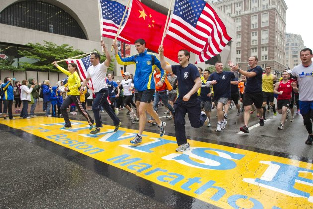 "Runners holding American flags and Chinese flag cross finish line after completing final mile of Boston Marathon course during ""#onerun"" in Boston"