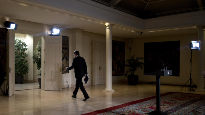 Spain's Prime Minister Mariano Rajoy walks away after making a speech at the Moncloa Palace in Madrid, Friday Dec. 28, 2012. In his end of year assessment, Mariano Rajoy said Friday the crisis had been worse than he had anticipated and that the first half of 2013 will be very hard, but that the economy should begin to recover in the second semester. Rajoy says the country's economy will be in recession for some time and faces a tough year ahead as it grapples with a deep financial crisis and 25 percent unemployment. (AP Photo/Paul White)