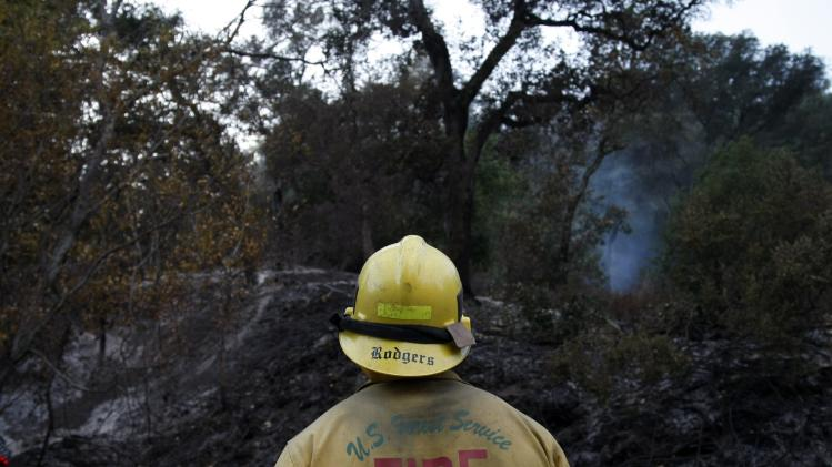 A firefighter assigned to the San Bernardino National Forest watches a scorched ridge following a burn out operation in Big Sur