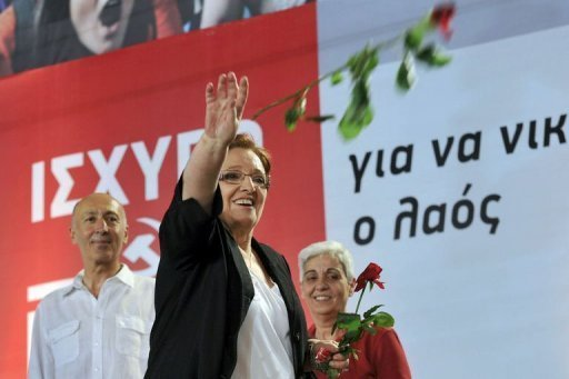 Communist party leader Aleka Papariga throws flowers to supporters at a pre-election rally in Athens Friday