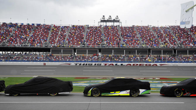 Cars are covered during a rain delay in the NASCAR Sprint Cup Series Aaron's 499 auto race at Talladega Superspeedway in Talladega, Ala., Sunday, May 5, 2013. (AP Photo/Rainier Ehrhardt)