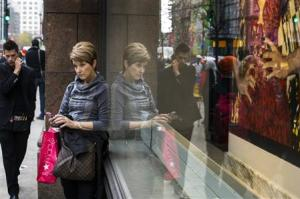 Woman stops to use her phone in front of holiday window displays at Macy's flagship store in New York