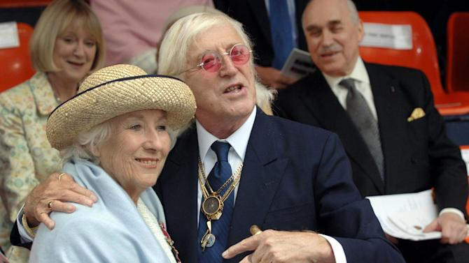 FILE In this Sunday Sept. 18, 2005 file photo Vera Lynn and Jimmy Saville, right are seen at the unveiling of a contemporary sculpture at Victoria Embankment in central London to mark the 65th anniversary of the Battle of Britain.  Friends and police say veteran British broadcaster Jimmy Savile, a famously eccentric popular culture figure, has died Saturday Oct. 29, 2011 at his home in northern England. He was 84. Savile, known for his garish tracksuits, chunky gold jewelry and boundless enthusiasm for pop music and charity work, was the host of two long-running British television programs and claimed to have been a confidant to the royal family.   (AP Photo/Matthew Fearn, Pool)