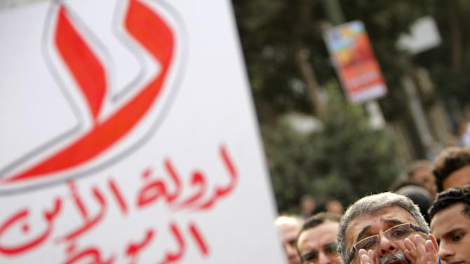"""An Egyptian protester shouts slogans as another holds anti-Muslim brotherhood banner reading, """"no for bloody state security,"""" during a protest in support of victims of Friday's clashes in the Nile Delta city of Mansoura, in Cairo, Egypt, Saturday, March 2, 2013. (AP Photo/Amr Nabil)"""