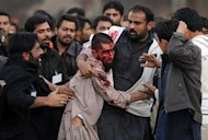 Pakistani Shiite Muslims assist an injured Sunni Muslim following clashes during an Ashura procession in Rawalpindi on November 15, 2013