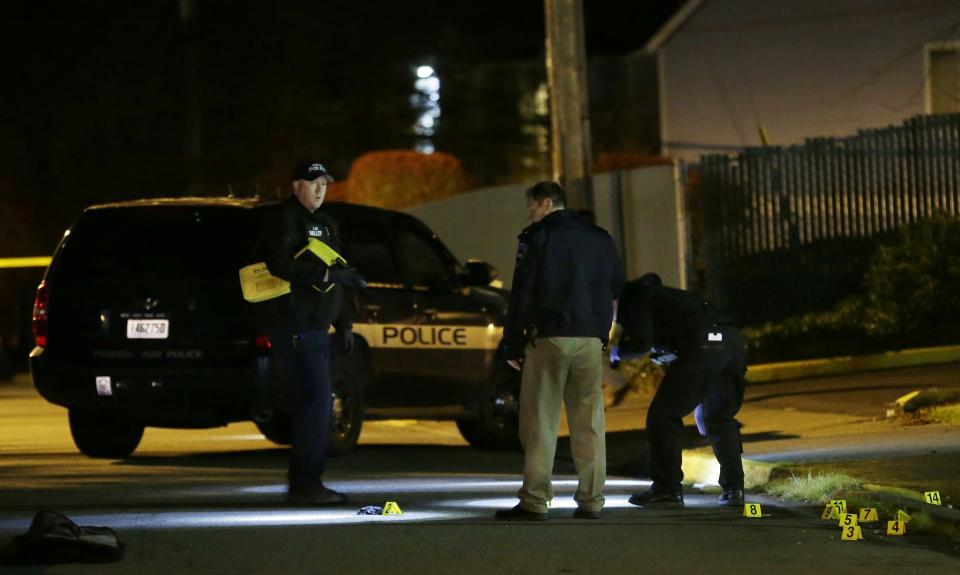 Police officers stand near evidence markers at the scene of an overnight shooting that left five people dead, Monday, April 22, 2013, at the Pinewood Village apartment complex in Federal Way, Wash. (AP Photo/Ted S. Warren)
