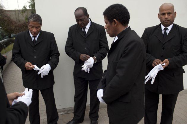In this July 2, 2013 photo, black pallbearers put on their white gloves as they prepare to handle a coffin during a burial in Lima, Peru. These pallbearers are in the job precisely because of the color of their skin, a phenomenon unique to this South American capital that was a regional seat of Spains colonial empire for more than three centuries and where racism remains so deeply ingrained that many Peruvians dont consider the practice discriminatory. (AP Photo/Rodrigo Abd)