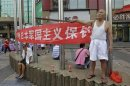 Protester yells anti-Japan slogans as he holds stick in front of banner on commercial street in Wuhan, Hubei province