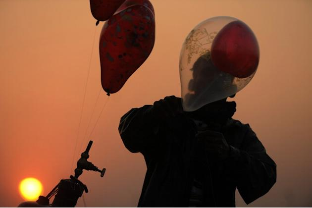 An Indian vendor inflates balloons as the sunsets in Siliguri on December 31, 2012. Sydney will kick off a wave of dazzling firework displays welcoming in 2013, from Dubai to Moscow and London, with l