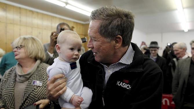 U.S. Republican presidential candidate and Ohio Governor John Kasich holds a baby during a campaign stop at Dukes Bar-B-Que in Orangeburg