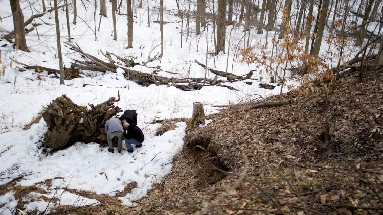 Historian Watson and brothers Bill and Earl Schandelmeier search for artifacts in the melting snow atop a tree trunk at the site of Duffy's Cut in Malvern