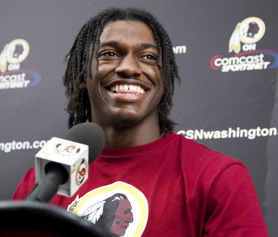 FILE - This May 6, 2012 file photo shows Washington Redskins quarterback Robert Griffin III talking to reporters following the team&#39;s rookie NFL football camp at Redskins Park in Ashburn, Va. Griffin has agreed to terms on a contract with the Redskins. Griffin&#39;s agent, Ben Dogra, told The Associated Press that the Heisman Trophy-winning quarterback agreed to terms and will be in Redskins rookie camp on Wednesday, July 18, 2012. (AP Photo/Manuel Balce Ceneta, File)
