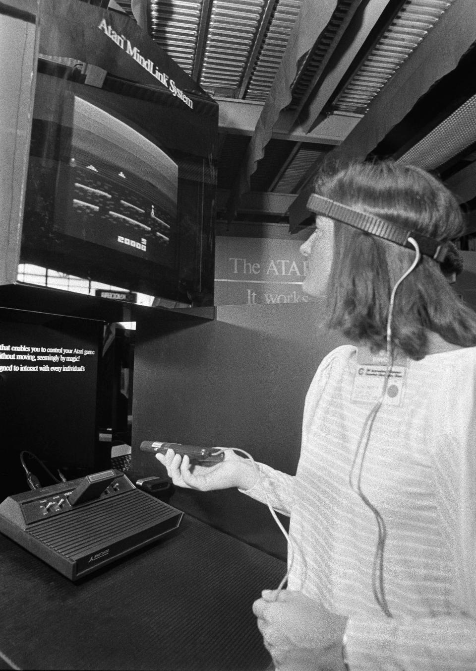 FILE- In this June 5, 1984, file photo, a woman in Chicago demonstrates Atari's new game, Mind Link, which utilizes a headband that picks up electrical impulse from the movement of the forehead and transmits them to a receiver attached to a video game or home computer console. (AP Photo/Charlie Knoblock)
