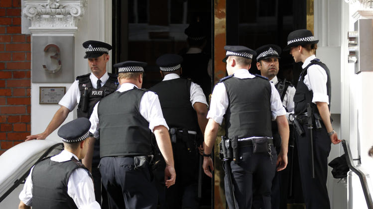 British police officers stand guard outside the Ecuadorian Embassy in central London, Thursday, Aug. 16, 2012. WikiLeaks founder Julian Assange entered the embassy in June in an attempt to gain political asylum to prevent him from being extradited to Sweden, where he faces allegations of sex crimes, which he denies. (AP Photo/Sang Tan)
