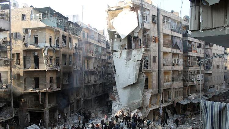 Syrians search for survivors amidst the rubble following an airstrike in Aleppo, on December 17, 2013