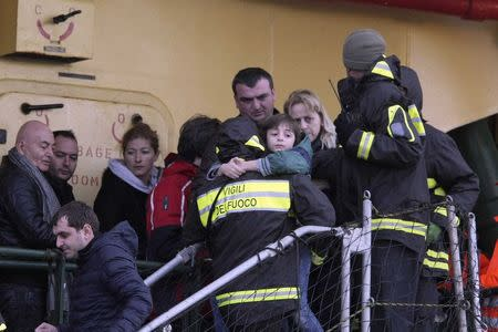 """Firefighter carries a child from the """"Spirit of Piraeus """" cargo container ship as they arrive at Bari harbour, after the car ferry Norman Atlantic caught fire in waters off Greece"""