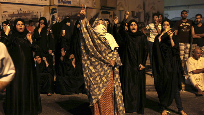 """Bahraini villagers shout anti-government slogans toward riot police who were cordoning off the nearby site where a youth was killed, allegedly by police shotgun fire,  in Sadad, Bahrain, early Saturday, Sept. 29, 2012. An Interior Ministry statement said a police patrol was attacked with petrol bombs and iron rods, and one person died when """"policemen defended themselves."""" A witness among protesters said demonstrators were marching against the government when a policeman suddenly stepped out near the youth and shot him at close range. (AP Photo/Hasan Jamali)"""