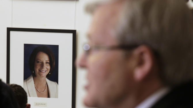 """Former Australian Prime Minister Kevin Rudd announces that he will contest a leadership ballot of his Labour Party in Canberra, Australia, Wednesday, June 26, 2013, as photo of Prime Minister Julia Gillard is displayed at the back. Prime Minister Julia Gillard threw open her job to an intra-party leadership ballot and the man she ousted three years ago, Rudd, stepped up to challenge her, saying their party will face a """"catastrophic defeat"""" without a change at the top. (AP Photo/Rick Rycroft)"""