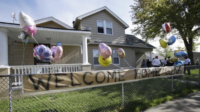 """A """"Welcome Home Gina """" sign hangs on a fence outside the home of Gina DeJesus  Tuesday, May 7, 2013, in Cleveland.  DeJesus, Amanda Berry and Michelle Knight, who went missing separately about a decade ago, were found in a home just south of downtown Cleveland and likely had been tied up during years of captivity, said police, who arrested three brothers. (AP Photo/Tony Dejak)"""