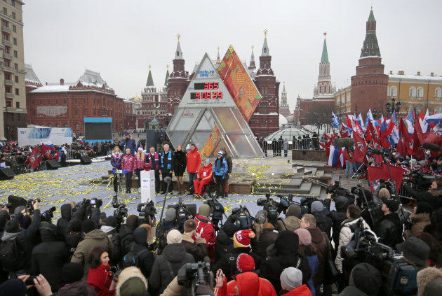 Moscow's Mayor Sergei Sobyanin, center, stands surrounded by a crowd of various sports enthusiasts waving Russian and Moscow flags during a ceremony of the launching the one-year count down clock for