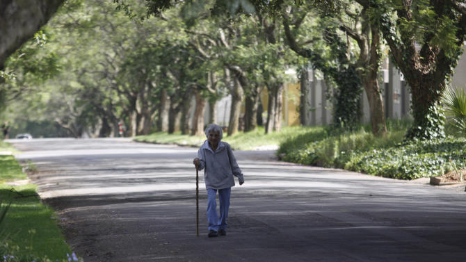 A elderley neighbour strolls past the Johannesburg home, unseen left, of former president Nelson Mandela's Friday, Dec. 28, 2012. Mandela who was admitted to hospital Dec 8, with a lung infection and underwent gall stone surgery, is now receiving medical care at home after being discharged Wednesday. (AP Photo/Denis Farrell)