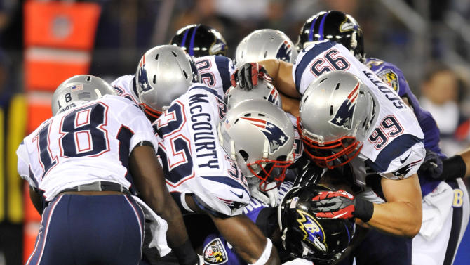 New England Patriots defenders tackle Baltimore Ravens wide receiver Deonte Thompson, bottom center, as he rushes the ball in the first half of an NFL football game in Baltimore, Sunday, Sept. 23, 2012. (AP Photo/Gail Burton)