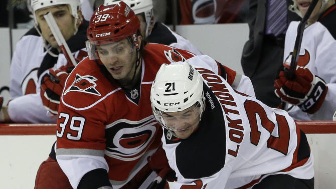 Carolina Hurricanes' Patrick Dwyer (39) and New Jersey Devils' Andrei Loktionov (21), of Russia, chase the puck during the second period of an NHL hockey game in Raleigh, N.C., Thursday, March 21, 2013. (AP Photo/Gerry Broome)