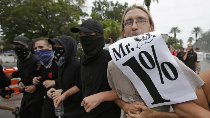 Demonstrators march in downtown St. Petersburg, Fla., Sunday, Aug. 26, 2012. The protestors were demonstrating near Tropicana Field where a welcoming event is taking place for the delegates of the Republican National Convention. (AP Photo/Dave Martin)