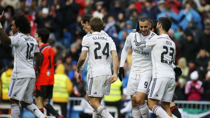 Real Madrid's Benzema is congratulated on his goal against Real Sociedad by team mate Isco during their Spanish first division match in Madrid