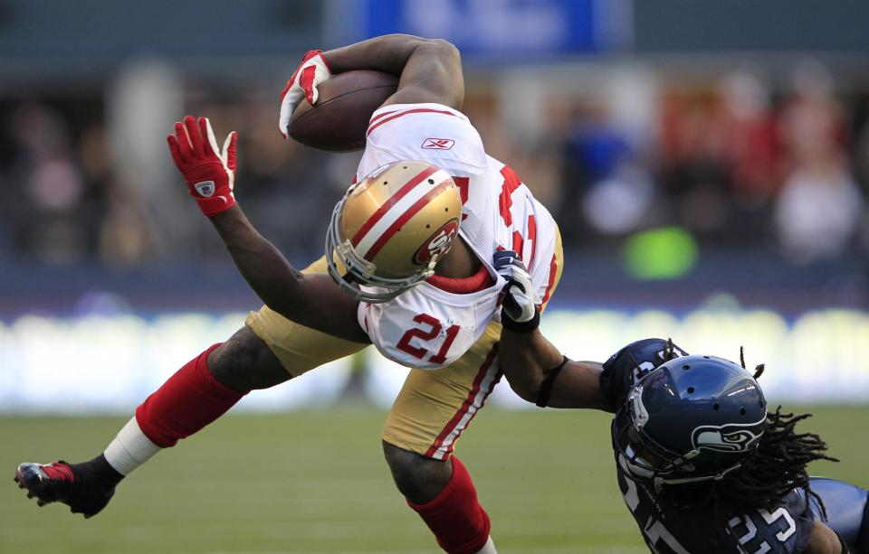 San Francisco 49ers'  Frank Gore (21) is grabbed by Seattle Seahawks'  Richard Sherman in the second half of an NFL football game in Seattle Saturday, Dec. 24, 2011. (AP Photo/John Froschauer)