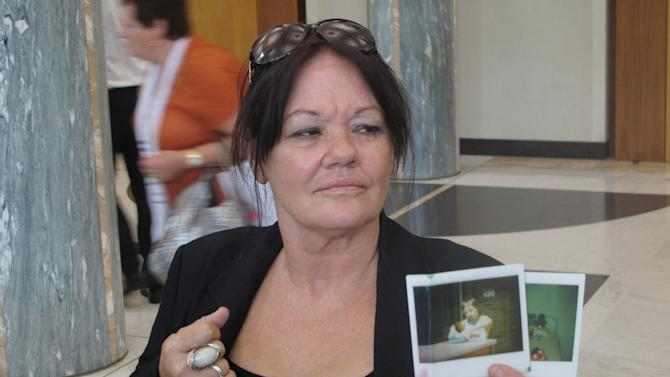 Christine Harms, 60, holds a photograph of her disabled son Kenneth at Parliament House in Canberra, Thursday, March 21, 2013. Kenneth was taken from her when she gave birth at 15. She came to Parliament House to a historic national apology delivered by Australian Prime Minister Julia Gillard to the thousands of unwed mothers who were forced by government policies to give up their babies for adoption over several decades.  (AP Photo/Rod McGuirk) )
