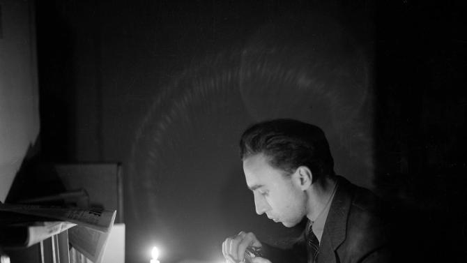 "FILE - In this February 1946 file photo, Associated Press correspondent George E. Bria works by candlelight in the AP Rome bureau during a power failure. Nine months earlier, Italy on Saturday, April 25, 2015,  celebrated the 70th anniversary of a partisan uprising against the Nazis and their Fascist allies at the end of World War II. The anniversary marks the day in 1945 when the Italian resistance movement proclaimed an insurgency as the Allies were pushing German forces out of the peninsula. Within days, Fascist dictator Benito Mussolini, who headed a Nazi puppet state in northern Italy, was captured, shot and hung by his feet in a Milan square, along with his mistress. ""He was on a train going to Switzerland disguised as a German,"" recalled George Bria, an Associated Press correspondent who covered the Allied push into Italy. ""Plain, ordinary German soldier, with his mistress and some other fascist officials, also disguised. Well, the partisans got wind of this and they captured them."" (AP Photo, File)"