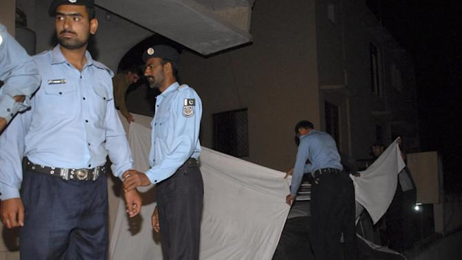 Police officers cover a vehicle to hide the family of Osama bin Laden from media, in Islamabad, Pakistan on Thursday, April 26, 2012. A minivan carrying the three widows and children of Bin Laden has left the house where they have been staying in Islamabad and is en route to the airport, from where they will be deported to Saudi Arabia, officials and witness said. (AP Photo/M. Yasir)