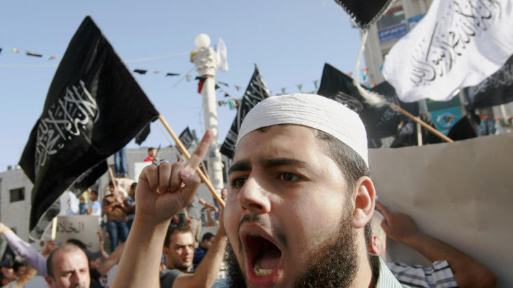 "Palestinian supporters of Hizbut-Tahrir, or Party of Liberation, shout slogans during a rally in the West Bank city of Ramallah, Tuesday, June 4, 2013. Arabic words on the flags read: ""There is no god but God, and Mohammed is his prophet."" A senior Palestinian official says the West Bank government will try to bring Israel up on charges through the U.N. if American attempts to restart peace talks fail. (AP Photo/Majdi Mohammed)"