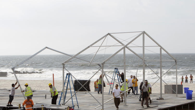 Construction workers disassemble a temporary building on the beach that was set up for an upcoming surfing competition in Long Beach, N.Y., Thursday, Aug. 25, 2011. The building was being being taken down to over concerns that it lies in the path of Irene, which is threatening to hit the East Coast.  (AP Photo/Seth Wenig)