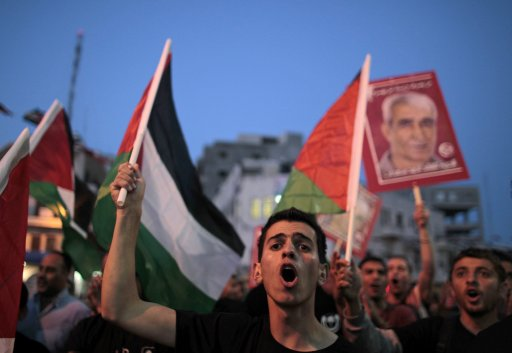 Palestinians wave flags as they celebrate the signing of a deal to end the Palestinian prisoners hunger strike, in Ramallah