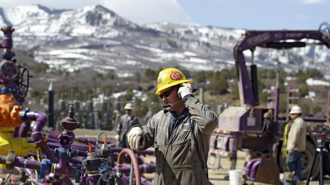 In this March 29, 2013 photo, a worker uses a headset and microphone to communicate with coworkers over the din of pump trucks, at the site of a natural gas hydraulic fracturing and extraction operation run by the Encana Oil & Gas (USA) Inc., outside Rifle, in western Colorado. The technique of hydraulic fracturing is used to increase or restore the rate at which fluids, such as petroleum, water, or natural gas can be recovered from subterranean natural reservoirs. (AP Photo/Brennan Linsley)