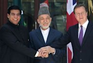 Britain's Prime Minister David Cameron (R), Pakistani Prime Minister Raja Pervez Ashfraf (L), and Afghan President Hamid Karzai shake hands before a meeting at the presidential palace in Kabul. Afghan efforts to negotiate with the Taliban need Islamabad's help if they are to be successful, the leaders of Afghanistan, Britain and Pakistan emphasised