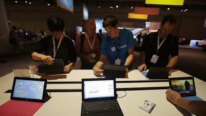 """Microsoft Surface Pro tablets are seen at a demo table at a Microsoft event in San Francisco, Wednesday, June 26, 2013. Microsoft on Wednesday released a preview version of an update to Windows 8, aiming to address some of the gripes people have with the company's flagship operating system. At a conference in San Francisco, Microsoft CEO Steve Ballmer acknowledged that the company pushed hard to get people to adopt a radical new tile-based """"Modern"""" user interface in Windows 8. Microsoft is now back-pedaling, making it easier to reach and use the older """"desktop"""" interface. (AP Photo/Jeff Chiu)"""