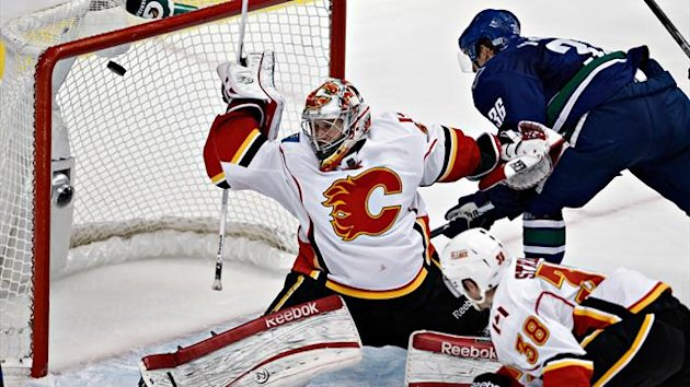 The puck goes past Calgary Flames goalie Leland Irving scored by Vancouver Canucks Jordan Schroeder during the third period of their NHL hockey game in Vancouver,